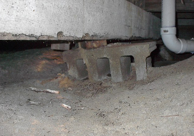 image of a sinking foundation pier under a house