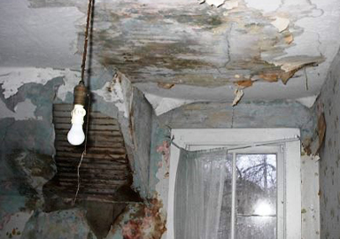 image of peeling paint, water damage, and mold on interior walls and ceiling of a home
